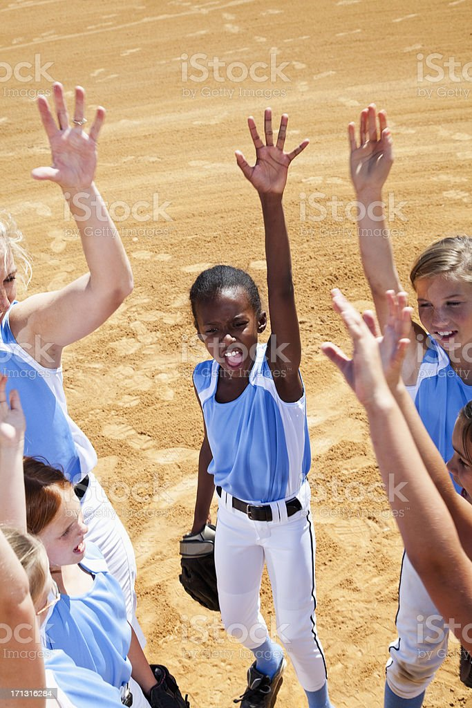 Softball players and coach doing team cheer stock photo