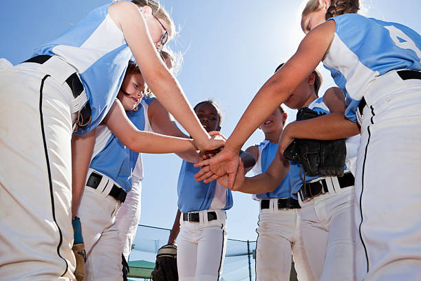 softball players with coach in huddle doing team cheer - softball stock photos and pictures