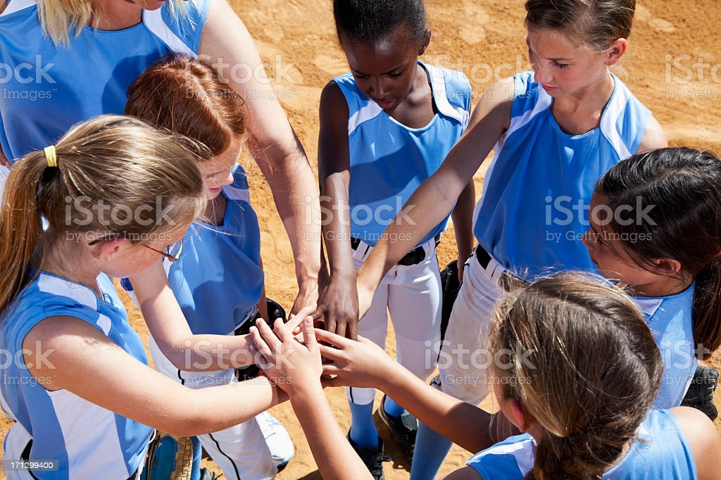 Softball players with coach in huddle doing team cheer stock photo