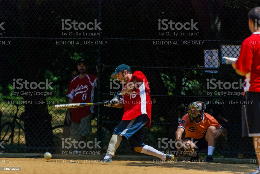 People playing softball on a field in central park with the batter...