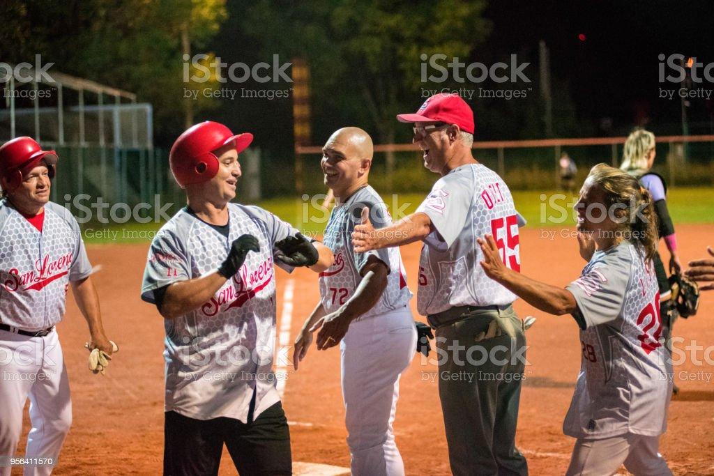 Softball Team Congratulating to a Player stock photo