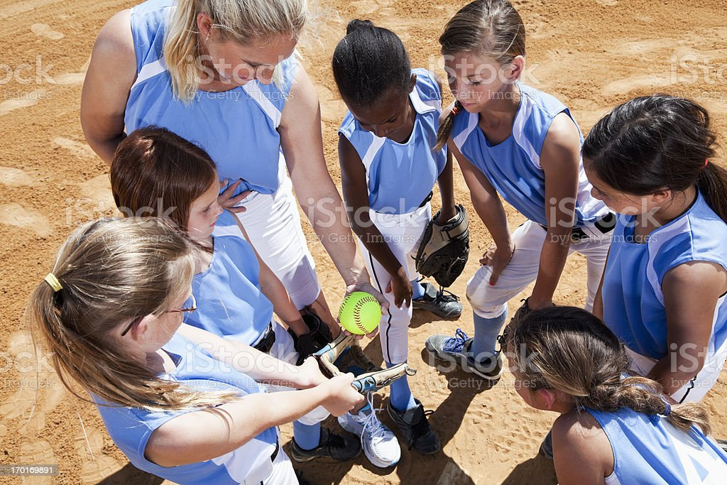 Softball team with coach in huddle royalty-free stock photo