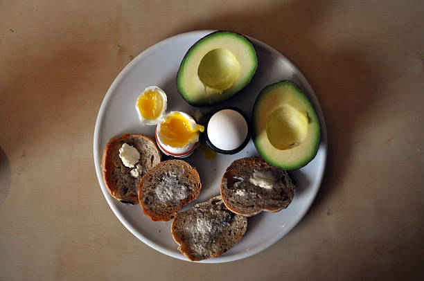Soft-boiled eggs, toast and an avocado stock photo