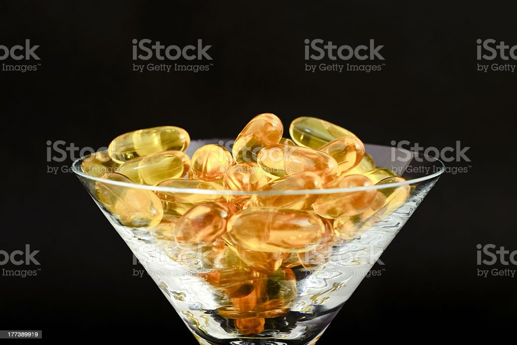 Softgel capsules in glass. royalty-free stock photo