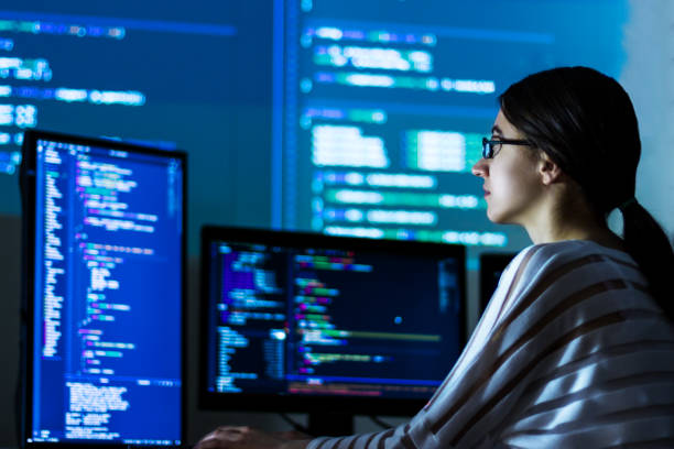 Software developer freelancer woman working at night Software developer freelancer woman female in glasses work with program code C++ Java Javascript on wide displays at night Develops new web desktop mobile application or framework Projector background computer language stock pictures, royalty-free photos & images