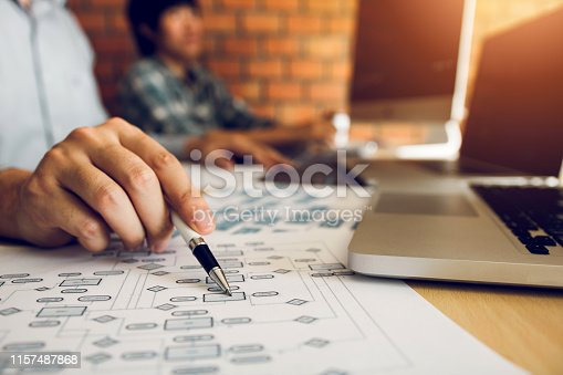 istock Software developer is pointing to the paper working and analyzing together the code written into the program on the computer. 1157487868