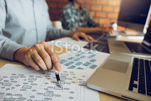 istock Software developer is pointing to the paper working and analyzing together the code written into the program on the computer. 1168146647