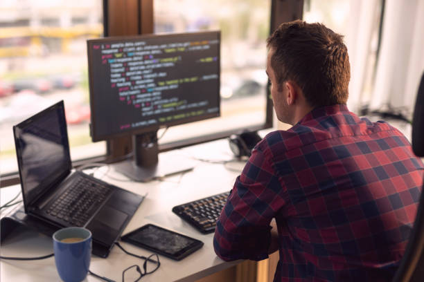 Software developer working Software developer working in a modern office broadcast programming stock pictures, royalty-free photos & images