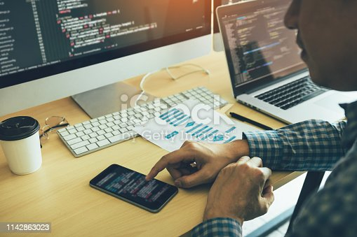 istock Software developers are using mobile phones to read the code. 1142863023