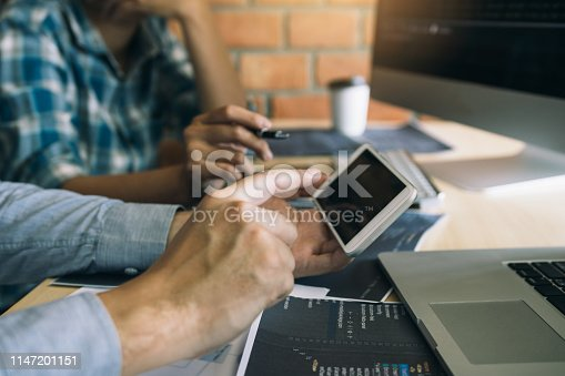istock Software developers are using smart phones and analyzing together the code written in the program on the computer. 1147201151