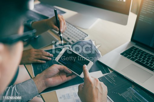 istock Software developers are using smart phones and analyzing together the code written in the program on the computer. 1152654365