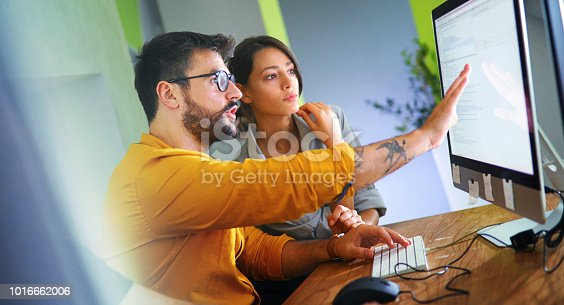Closeup side view of couple of mid 20's software developers resolving some issues with the code they're currently working on.