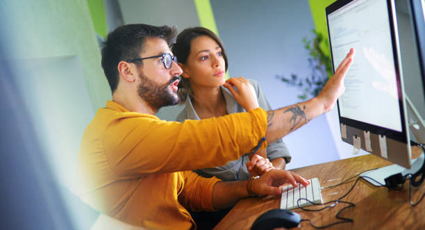 Software developers doing some research. Closeup side view of couple of mid 20's software developers resolving some issues with the code they're currently working on. web designer stock pictures, royalty-free photos & images