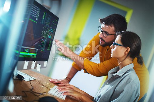 Closeup side view of couple of mid 20's software developers resolving some issues with the code they're currently working on.  NOTE: code lines on the screen are imaginary and blurred.