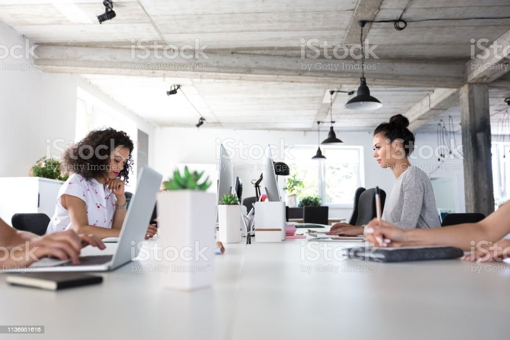 Software engineers working in modern office Shot of business women working around the table in modern work place. Adult Stock Photo