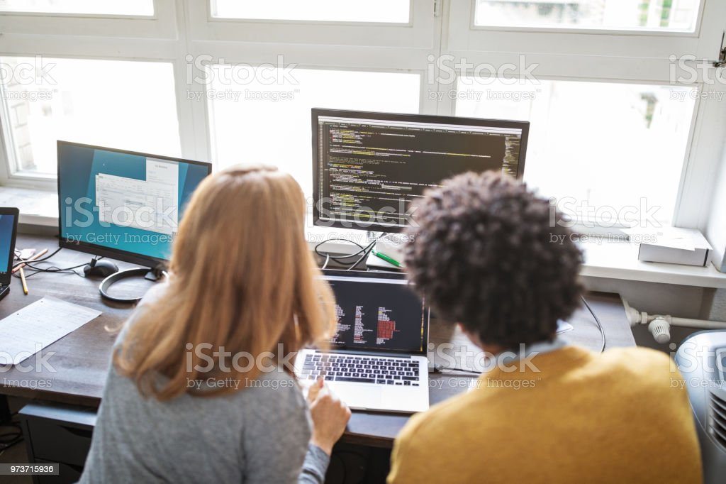 Software engineers working together on new project Rear view of male and female computer programmers working on a new project together in office. Software engineers working together at their desk. Adult Stock Photo