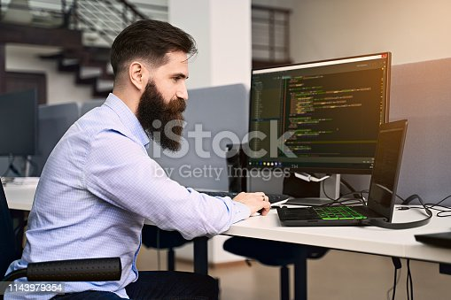 istock Software programming. Bearded man working on computer in IT office, sitting at desk writing code, working on a project in software development company or startup. High quality image. 1143979354