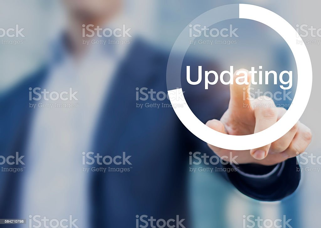 Software updating button with person touching button on the screen stock photo