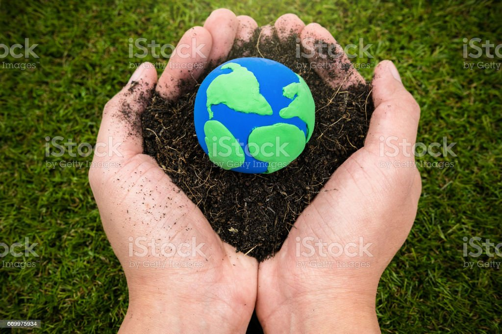 Soil  and earth simulation in hand on grass background, earth day concept stock photo