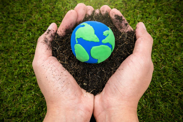 soil  and earth simulation in hand on grass background, earth day concept - earth day stock pictures, royalty-free photos & images