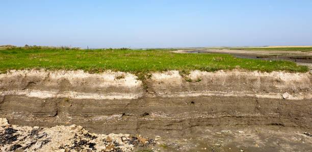 Soil layers in the dry salt marsh creek stock photo