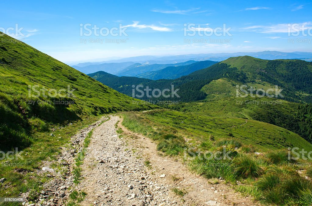 Soil road in mountains on background blue sky in summer stock photo