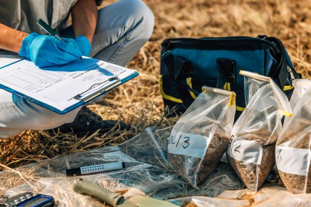 badanie gleby. kobieta agronom robi notatki w terenie - geologia zdjęcia i obrazy z banku zdjęć