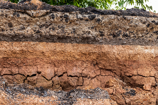 Low view, close-up, soil surface cross section under the asphalt road that is water eroded in Thai countryside.
