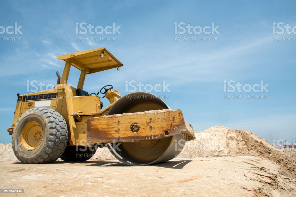 soil vibration roller during sand compacting works at construction site stock photo