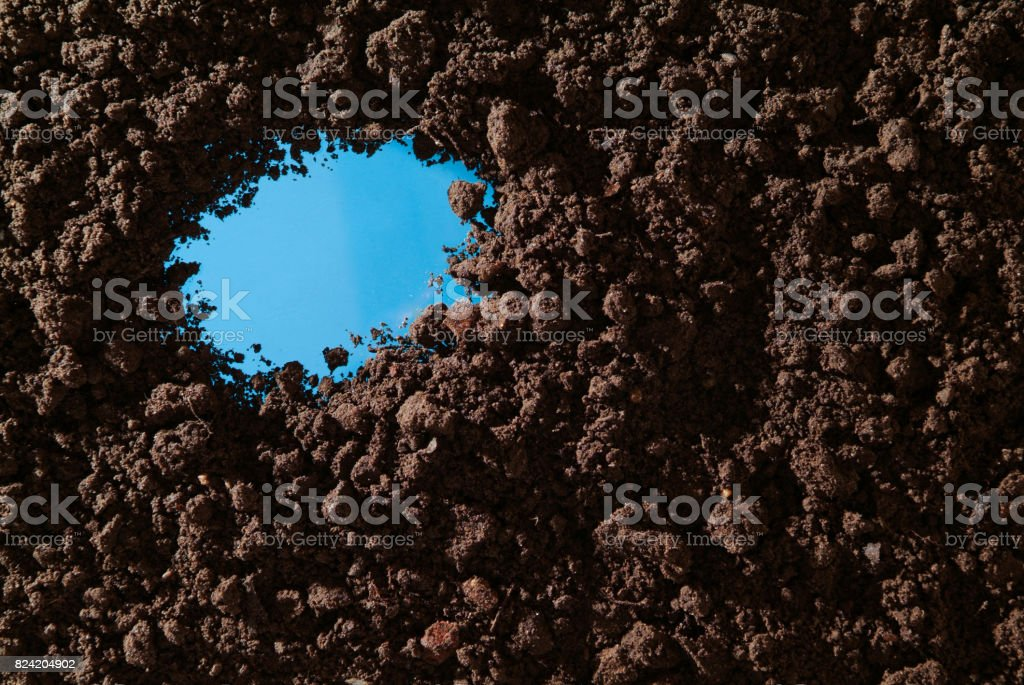 Soil with a hole in key blue stock photo