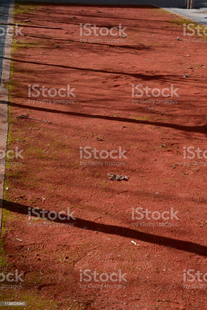 soiled and unkempt bocce court in the spring with the long shadows of trees in the sun stock photo