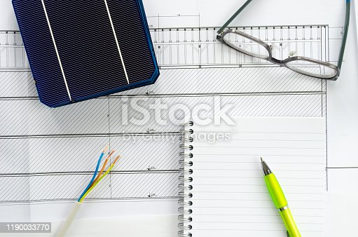 904490858 istock photo Solar cells, notepad, pen, eyeglasses and electrical cable as a concept of planning for photo voltaic project 1190033770