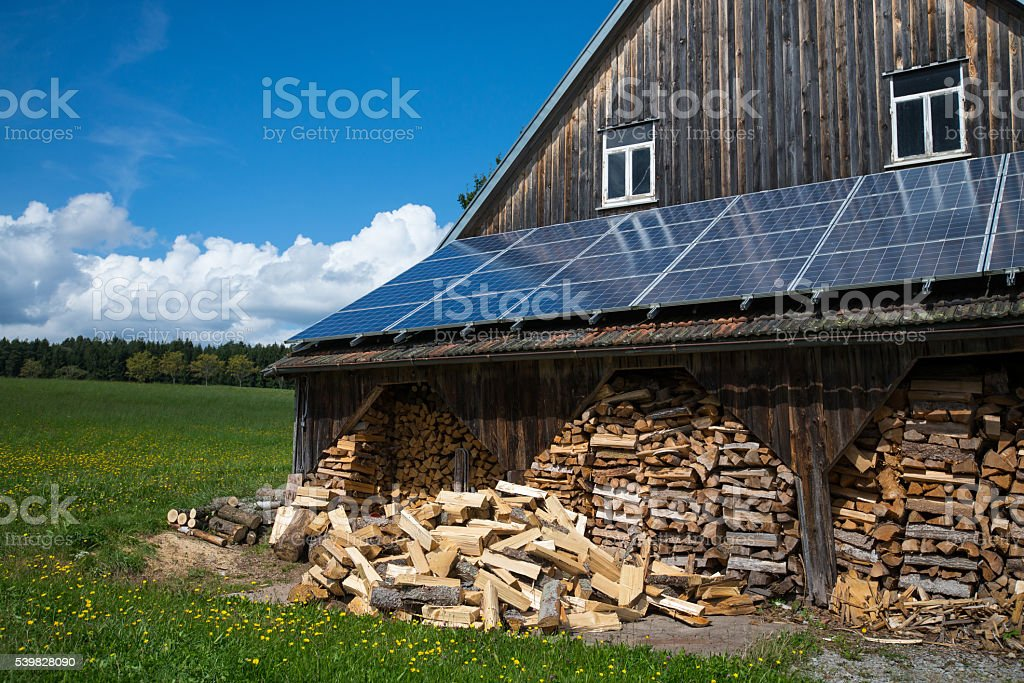 solar collector with fire wood at barn stock photo