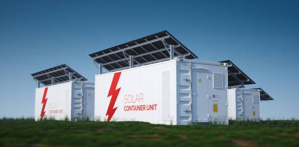 Solarcontainer-Einheit. 3d Rendering Konzept eines weißen industriellen Batterie-Energiespeicher-Container mit montierten schwarzen Sonnenkollektoren auf frischem grünem Gras bei spätem sonnigem Wetter. – Foto