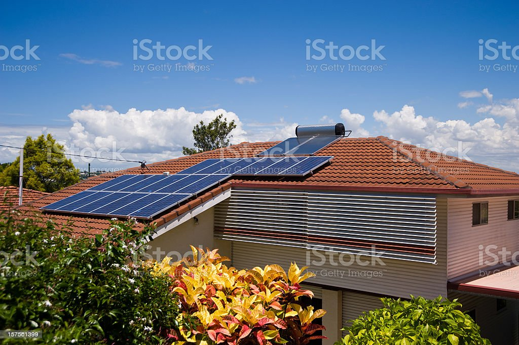 Solar Electricity and Hot Water System on house roof stock photo