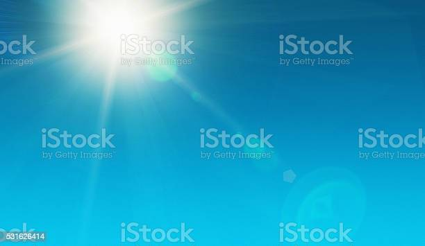 Looking up at the dazzling sun, high in the noonday sky and showing natural zoom lens flare. The source of our solar power. Ample copy space on sky.