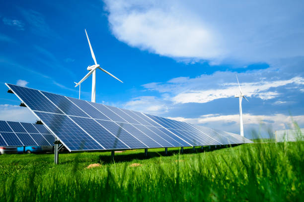 solar energy panels and windmills against blue sky on summer day - energia solare foto e immagini stock