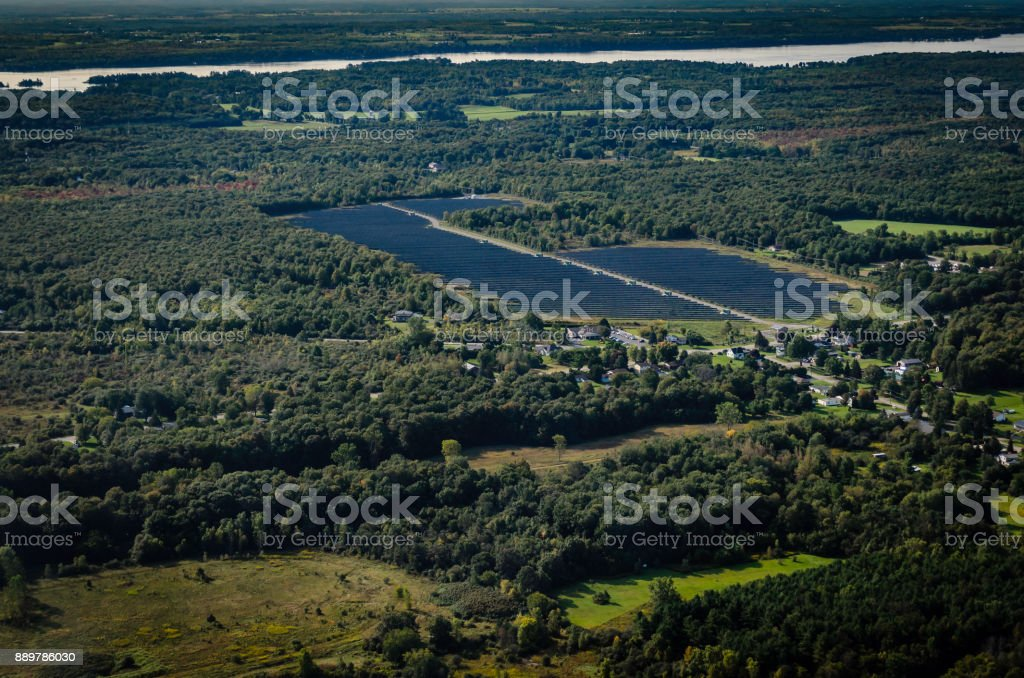 Solar Farm near the  St. Lawrence River in Ontario, Canada with the US shore in the distance. stock photo