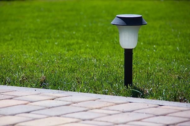 solar laterne in der nähe der befestigten garden path - solarleuchten stock-fotos und bilder
