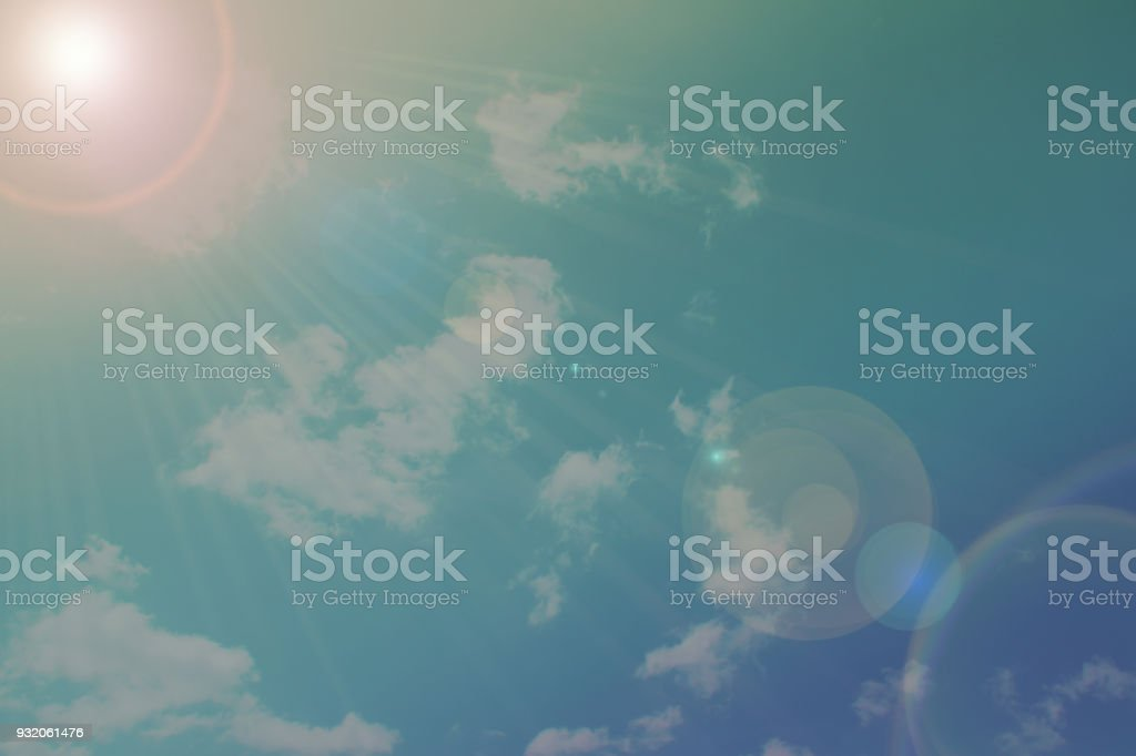 Solar lens flare.Beam of sun and sunlight bokeh on cloudy and blue...