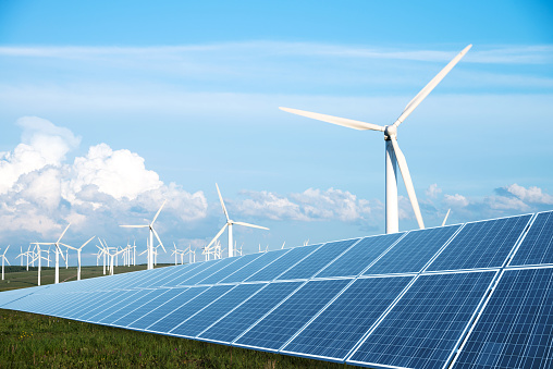 Solar Panel In Green Lawn With Wind Power Station Stock Photo - Download Image Now