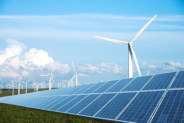 solar panel in green lawn with wind power station stock photo