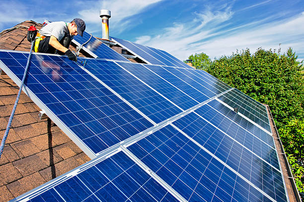 Solar panel installation Man installing alternative energy photovoltaic solar panels on roof solar panels photos stock pictures, royalty-free photos & images