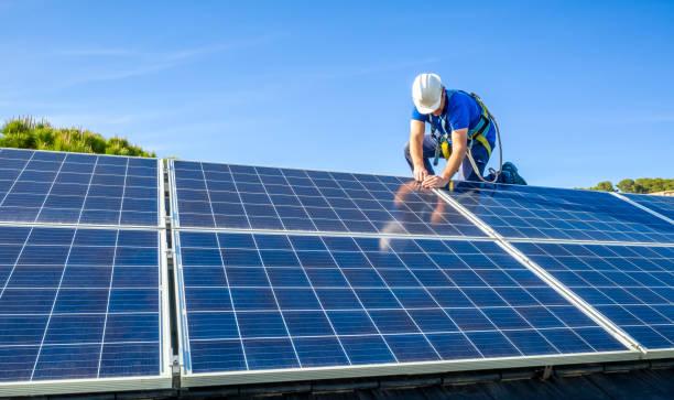 Solar panel installer installing solar panels on roof of modern house stock photo
