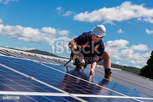Solar panel installer with drill installing solar panels on roof on a sunny day