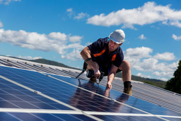 Solar panel installer with drill installing solar panels Solar panel installer with drill installing solar panels on roof on a sunny day solar panels photos stock pictures, royalty-free photos & images