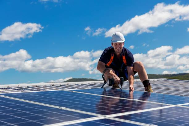 Solar panel installer with drill installing solar panels stock photo