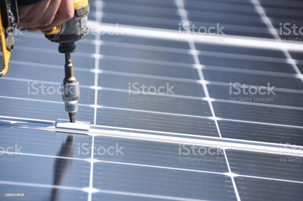 Solar panel installer with drill Solar panel installer with drill Adult Stock Photo