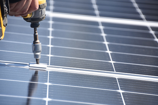 Solar Panel Installer With Drill Stock Photo - Download Image Now