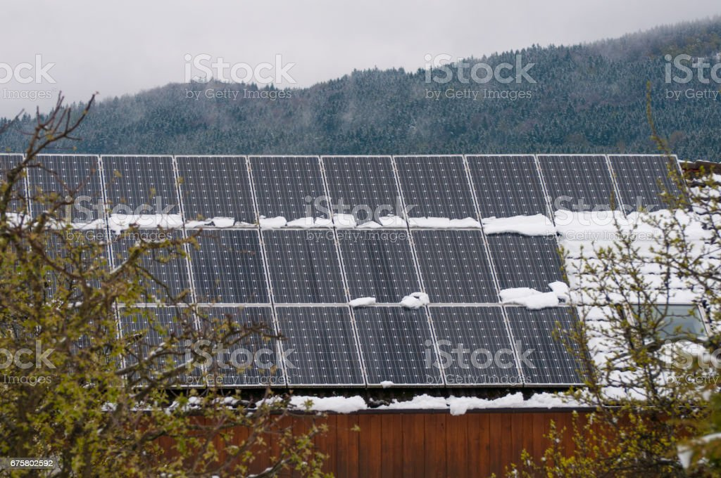 Solar panel on a red roof reflecting the sun and the cloudless blue sky stock photo